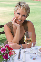 Woman drinking wine outdoors, portrait