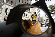 Carlos Hernandez, a local maintenance worker at a hotel, takes a cell phone photo of a broken traffic light left by the strong winds of Hurricane Matthew as it made its way up the East Coast, Saturday, Oct. 8, 2016, in downtown Savannah, Ga. (AP Photo/Stephen B. Morton)