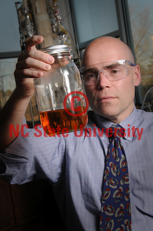 Bill Roberts looks over biofuel created in his lab.