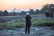 UNITED KINGDOM, London: 12 May 2020 <br /> A walker stops to take pictures of the London city skyline amongst a frosty Richmond Park early this morning. The weather in the capital, although starting sunny and cold today, is set to be cloudy for the rest of the week.