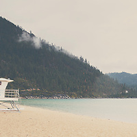 an empty beach & lifeguard tower on the edge of Lake Tahoe