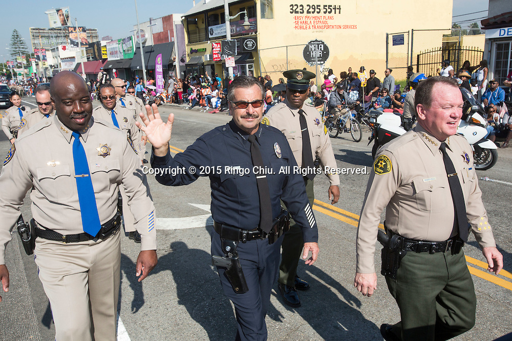 "Los Angeles Police Department Chief Charlie Beck and Los Angeles County Sheriff Jim McDonnell wave to the parade goers in the 30th annual Kingdom Day Parade in Los Angeles on Monday Jan. 19, 2015. The parade is Southern California's largest Martin Luther King Jr. Day observance. The theme of this year's parade was ""Love and respect, let it begin with me.""Photo by Ringo Chiu/PHOTOFORMULA.com)"