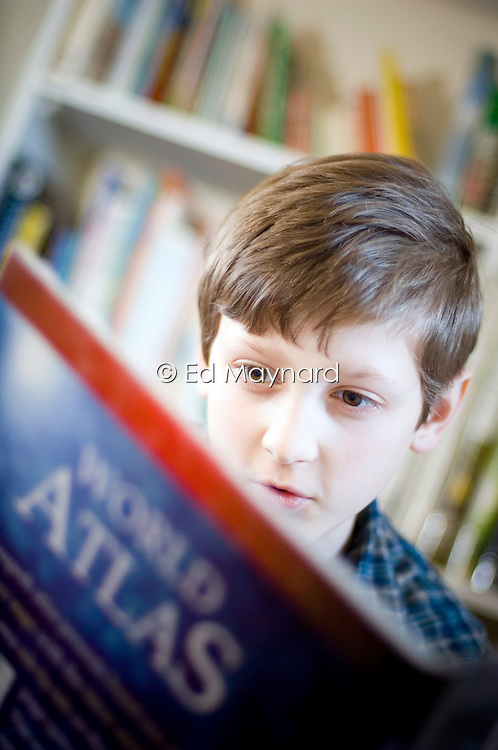 Ten year old boy looking at an atlas of the world, England, United Kingdom.