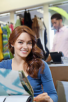 Portrait of beautiful young woman with textile samples while man in background