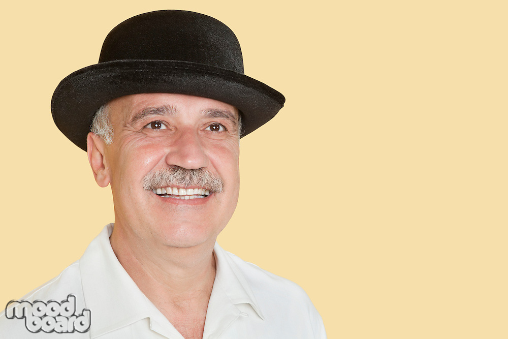 Happy senior man wearing hat while looking up over yellow background