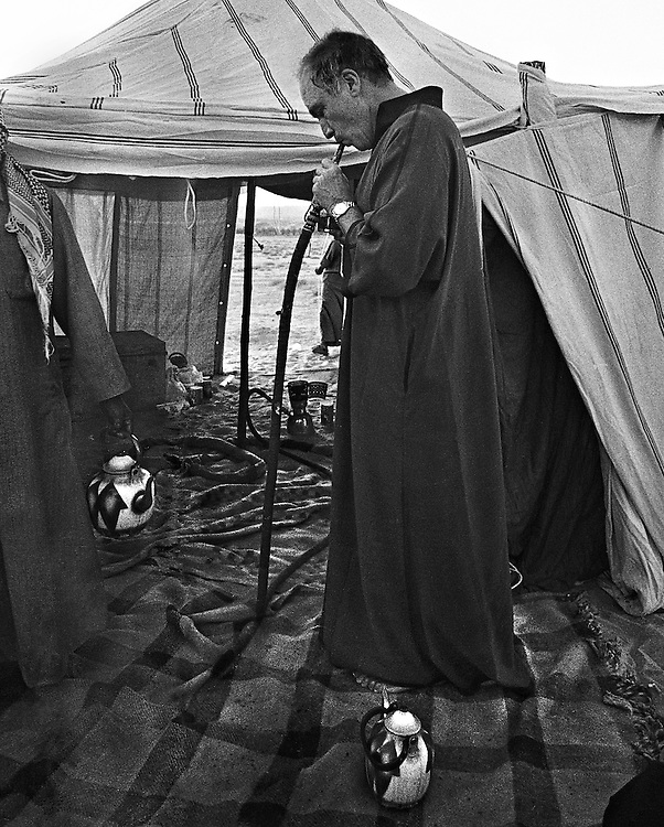 Canadian Prime Minister Pierre Trudeau tries a hooka pipe while camping in the desert near Mada'in Saleh, Saudi Arabia. (1980)