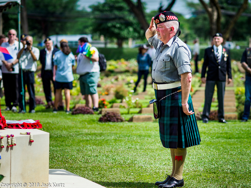 """11 NOVEMBER 2018 - KANCHANABURI, KANCHANABURI, THAILAND: STEWART WILSON, a Scottish veteran of the British army, salutes after placing a wreath on a memorial for soldiers killed working on the """"Death Railway"""" during the Rememberance Day ceremony at the Kanchanaburi War Cemetery in Kanchanaburi, Thailand. Kanchanaburi is the location of the infamous """"Bridge On the River Kwai"""" and was known for the """"Death Railway"""" built by Japan during World War II using allied, principally British, Australian and Dutch, prisoners of war as slave labor. There are 6,982 people buried in the cemetery, including 5,000 Commonwealth soldiers and 1,800 Dutch soldiers. November 11, 2018 marked the 100th anniversary of the end of World War I, celebrated as Rememberance Day in the UK and the Commonwealth and Veterans' Day in the US.    PHOTO BY JACK KURTZ"""