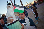 "30 DECEMBER 2008 -- PHOENIX, AZ: A Palestinian boy holds up his ""Ancestor Doll,"" a school project, during a pro-Palestinian protest in Phoenix Tuesday. About 200 people from a variety of human rights and peace activists organizations in Phoenix, AZ, marched in opposition to the Israeli attacks on Gaza and in favor of Palestinian rights on Tuesday, the fourth day of Israeli air strikes on Hamas facilities in Gaza. Photo by Jack Kurtz / ZUMA Press"