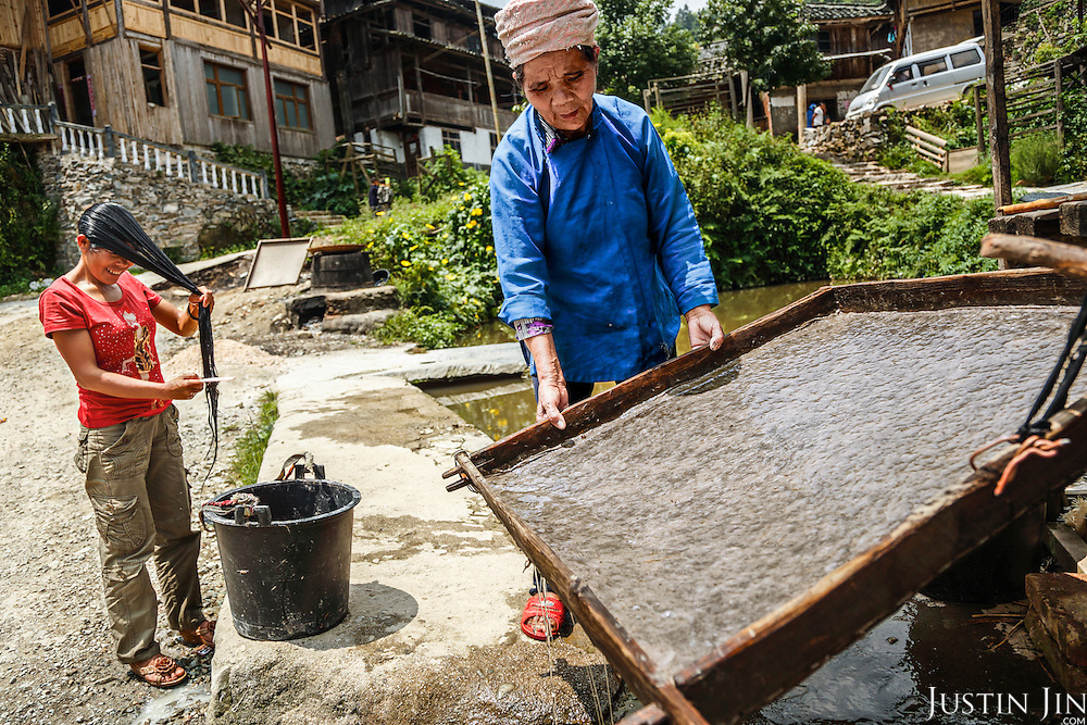 An old woman makes paper the traditional way, using weed pulp.