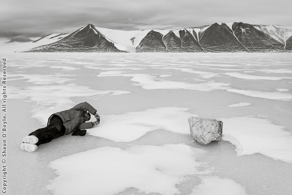 Sam Bowser getting the best angle on a boulder that rolled down Mt. Barnes onto the sea ice. Herbertson Glacier can be seen 5 miles away across New Harbor.