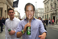 Pall Mall, London, UK  29/04/2011. The Royal Wedding of HRH Prince William to Kate Middleton. A reveller drinking beer through the face of Prince William on Pall Mall. Photo credit should read PAUL TREACY/LNP. Please see special instructions. © under license to London News Pictures