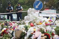 March 18, 2019 - Christchurch, New Zealand - Flower rest at a road block, as two police officers stand guard outside the Al Noor mosque in Christchurch, New Zealand on March 17, 2019. At least 50 people were killed and 36 injured in mass shootings at two mosques in the New Zealand city of Christchurch Friday, 15 March. A 28-year-old Australian born man appeared in Christchurch District Court on Saturday charged with murder. (Credit Image: © Sanka Vidanagama/NurPhoto via ZUMA Press)