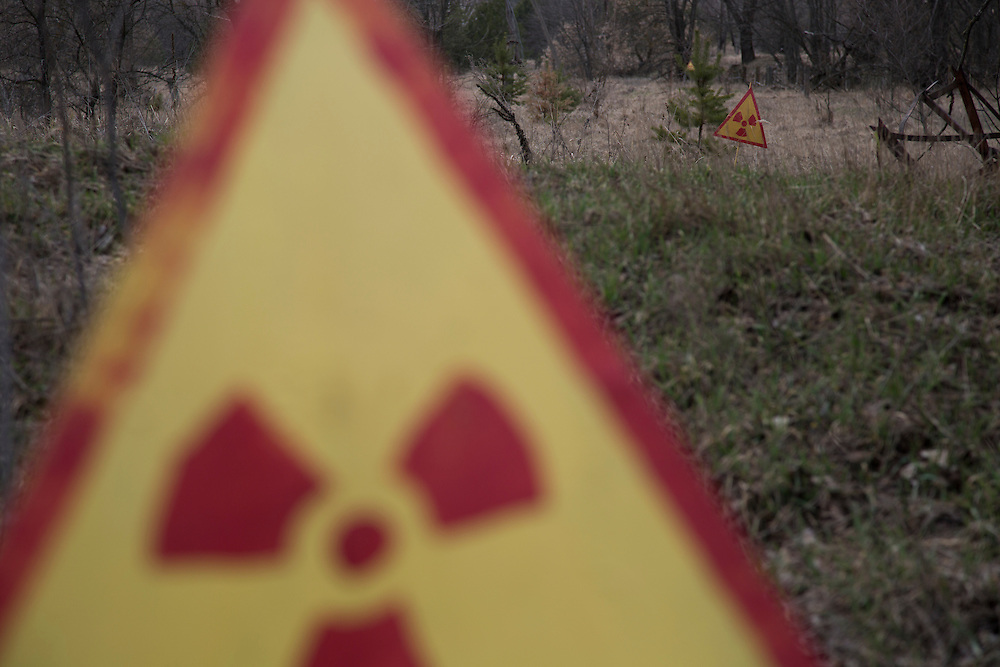 Hand painted signs warn of high levels of radiation on the edge of a buried village near the nuclear power plant.