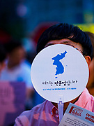 "15 JUNE 2018 - SEOUL, SOUTH KOREA:  A woman holds up a placard showing a unified Korea during a rally to mark the anniversary of the signing of the June 15th North–South Joint Declaration between South Korea and North Korea. The Declaration was negotiated by late South Korean President Kim Dae-jung and North Korean leader Kim Jong-il and signed on 15 June 2000. It was a part of South Korea's ""Sunshine Policy,"" which guides the South's relationship with North Korea. This year's observance of the anniversary was bolstered by the recent thawing in relations between North Korea and South Korea and the US.     PHOTO BY JACK KURTZ"