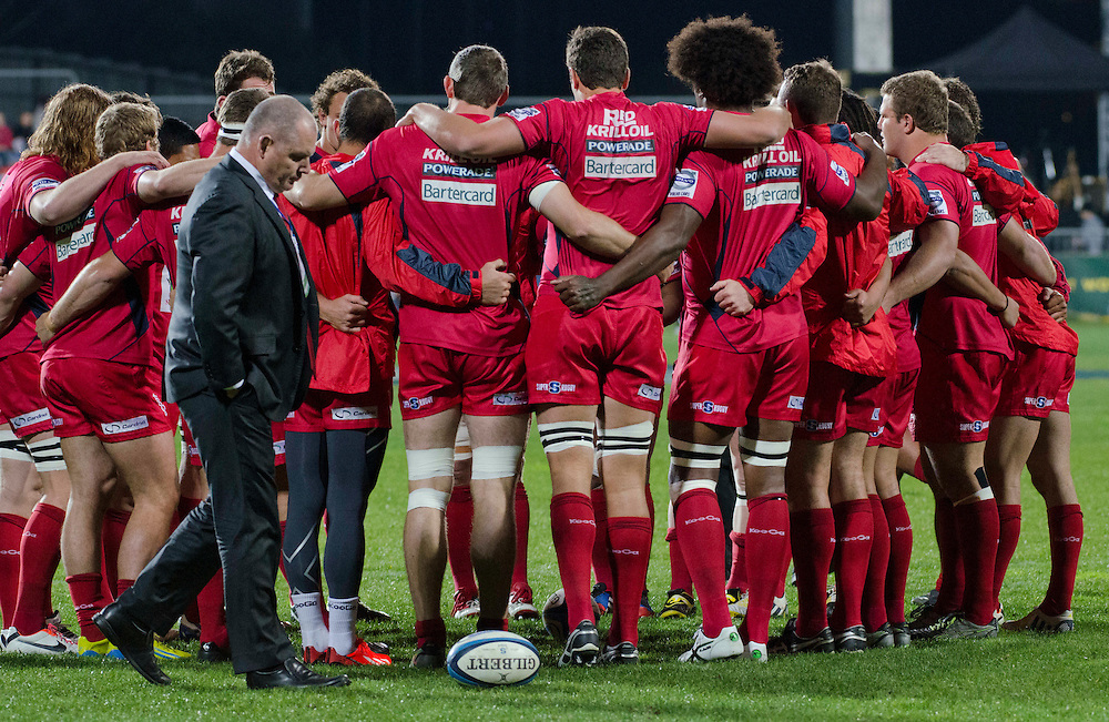 Reds coach Ewen McKenzie walks past a team huddle before the game against the Crusaders in the Super Rugby qualifier match at AMI Stadium, Christchurch, New Zealand, Saturday, July 20, 2013. Credit:SNPA / David Alexander