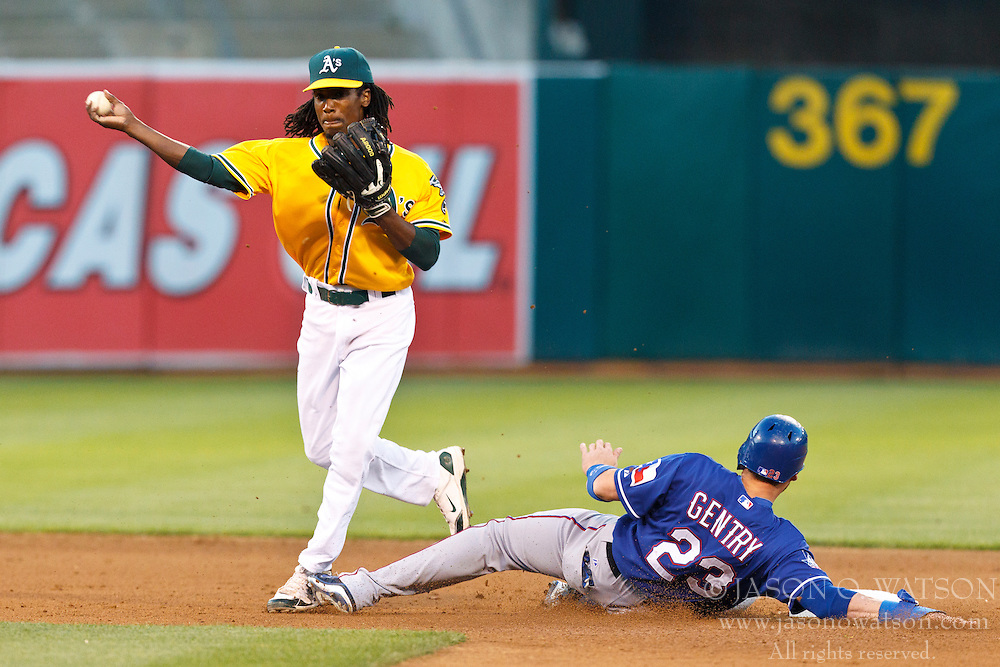 OAKLAND, CA - JULY 17: Jemile Weeks #19 of the Oakland Athletics completes a double play over Craig Gentry #23 of the Texas Rangers during the fourth inning at O.co Coliseum on July 17, 2012 in Oakland, California. (Photo by Jason O. Watson/Getty Images) *** Local Caption *** Jemile Weeks; Craig Gentry