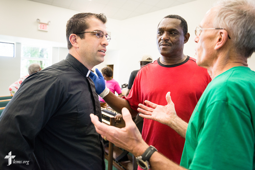 The Rev. Ross Johnson, director of LCMS Disaster Response (left) talks to the Rev. Clarence Martin (center) of St. Matthew Lutheran Church and the Rev. Rory Hermann of Good Shepherd Lutheran Church in Gulf Breeze, Fla., as volunteers remove the damaged carpet in the sanctuary of St. Matthew in Pensacola, Fla., on Saturday, May 3, 2014. Torrential rainfall led to widespread flooding in the area, damaging the sanctuary and fellowship hall of the church. LCMS Communications/Erik M. Lunsford