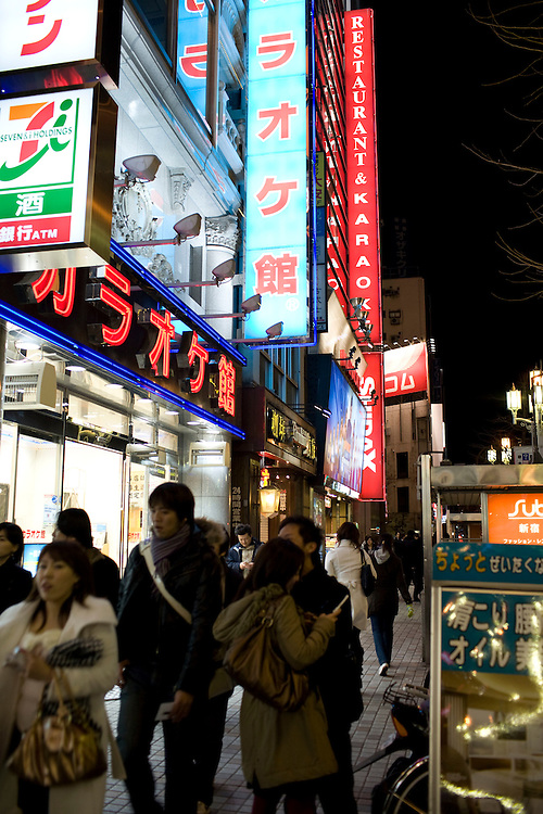 Typical Street in the entertainment district of an large Japanese City  with  many signs advertising Karaoke and  Room Restaurants  where groups of Japanese gather to eat  drink and sing together.  kabukicho near shinjuku station.