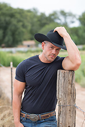 portrait of a handsome cowboy leaning on a wooden post