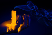 A hand holds a glowing candle that has been snuffed out,its wick leaving a ghostly trail of smoke.Black light