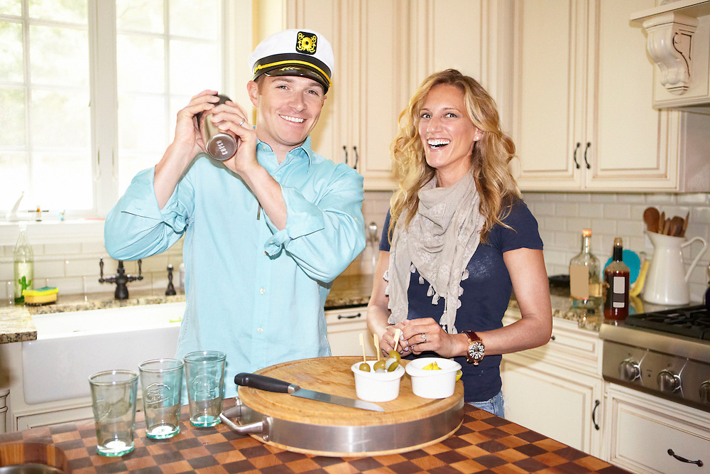 Lifestyle image of smiling couple making a cocktail drink inside home kitchen