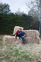 Boy with dog on hay bale