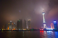 A night view of the Oriental Pearl Tower and Shanghai city skyline on the Huangpu River, on the Pudong side of Shanghai, China.  Shanghai is one of China's most important cultural, commercial, financial, industrial and communications centers.  It is also one of the busiest ports in the world and is a major economic center.