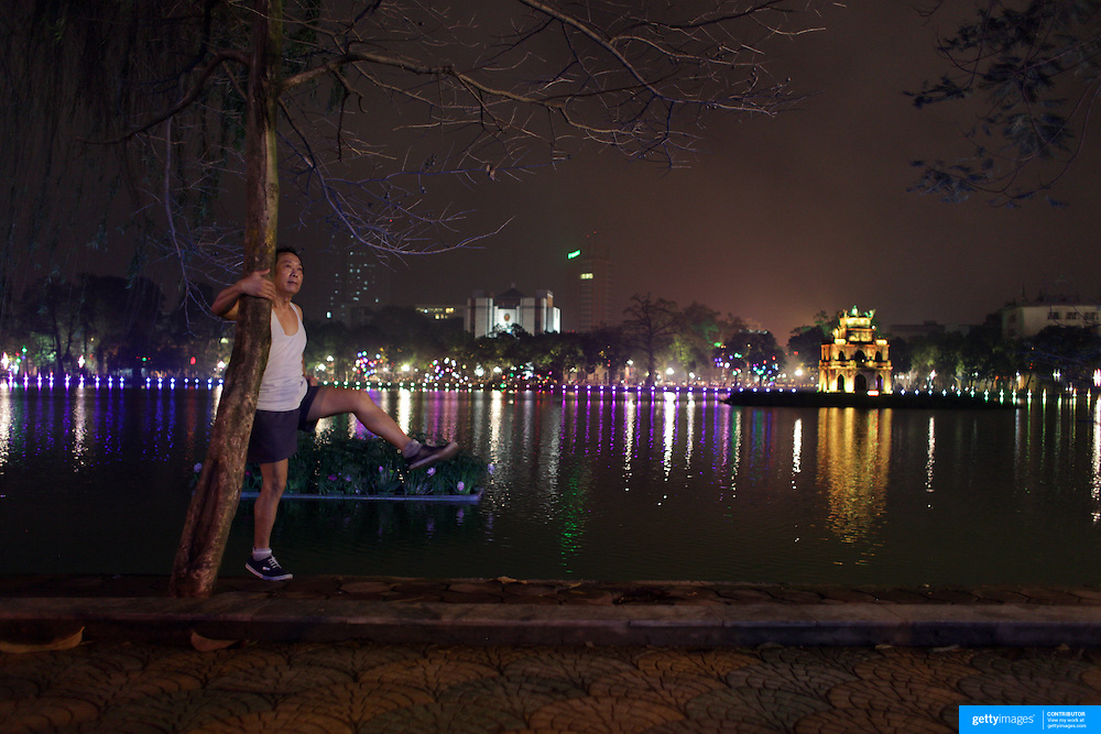 An elderly Vietnamese gentleman stretches in the early evening beside Hoan Kiem Lake, Hanoi, with the Thap Rue Pagoda visible in the distance.. For a county not know for it's sporting prowess, Hanoi, Vietnam's capital, appears to be gripped in a fitness frenzy. Before 6am street corners, parks and lake sides are a hive of activity as keep fit classes, Tai chi and personal exercise regimes are seen in abundance around the city. Particularly noticeable are Women's keep fit classes, often accompanied by loud poor quality western disco beat music as the occupants of the city get fit come rain or shine. Hanoi, Vietnam. 19th March 2012. Photo Tim Clayton