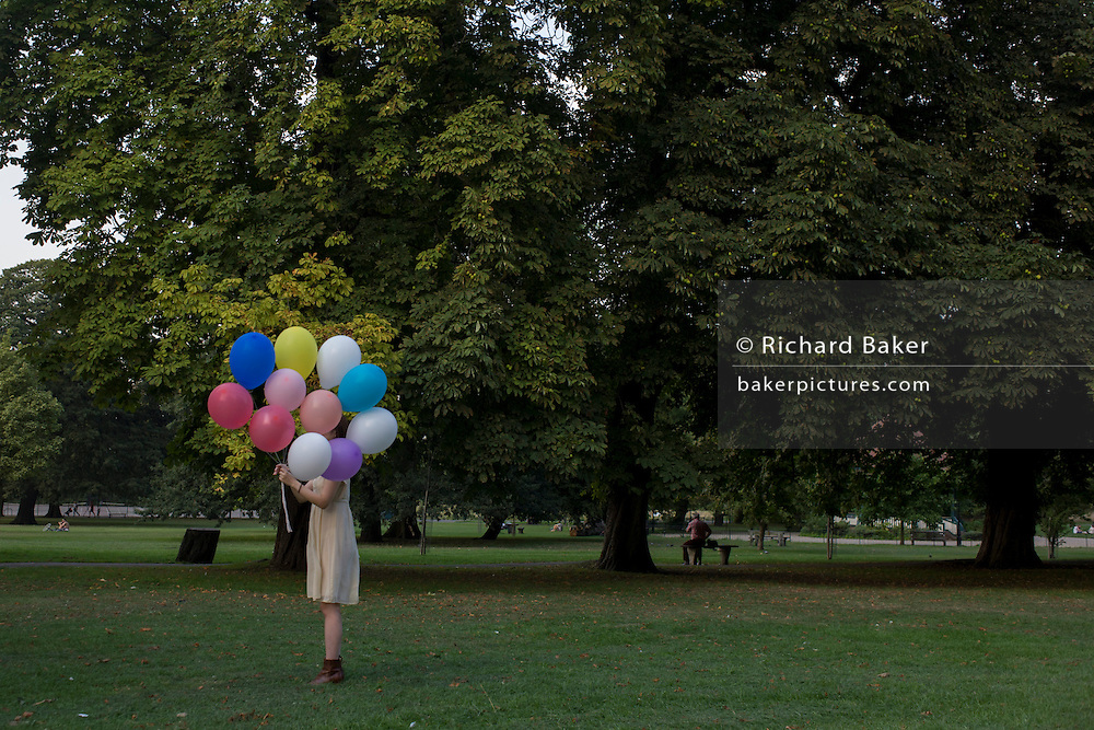 An anonymous girl stands holding a bunch of inflated balloons in a south London park.