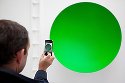 © Licensed to London News Pictures. 09/10/2012. LONDON, UK.  A gallery visitor uses a mobile phone to take a picture of Anish Kapoor's sculpture 'Green' (2012) at a press view ahead of his new exhibition at the Lisson Gallery in London today (09/12/12) . The exhibition, the first since the artists solo exhibition at the Royal Academy of the Arts in 2009, features new works by Kapoor and runs from the 10th of October to the 10th of November 2012. Photo credit: Matt Cetti-Roberts/LNP