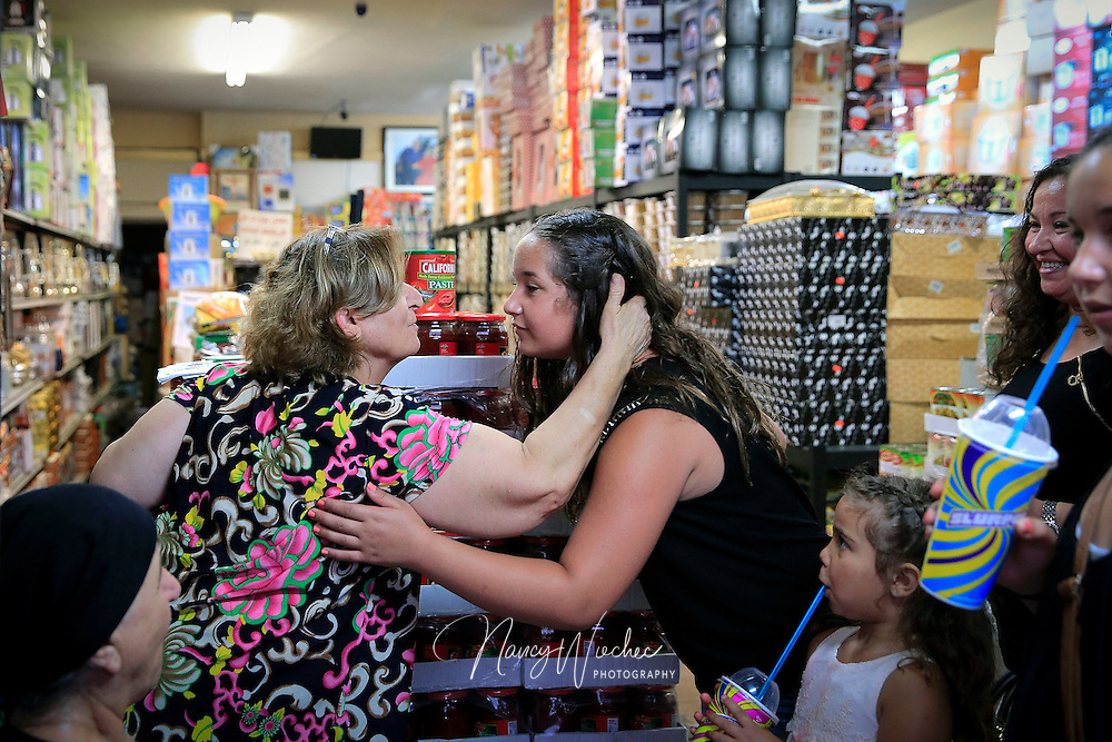 Chaldean Nancy Shimon greets customers at her spice shop near Main Street in El Cajon, California, Aug. 14, 2015. Amid a variety of Middle Eastern spices, grocery goods and sundries, the store stocks Catholic statues, rosaries and crucifixes. (Nancy Wiechec for ONE magazine)