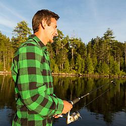 A man fishing on Long Pond near the Appalachian Mountain Club's Gorman Chairback Lodge. Near Greenville, Maine.