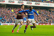 Glen Kamara (#18) of Rangers FC holds off Jamie Walker (#10) of Heart of Midlothian FC during the Ladbrokes Scottish Premiership match between Rangers FC and Heart of Midlothian FC at Ibrox Park, Glasgow, Scotland on 1 December 2019.