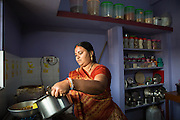 Shantilal's wife, Maya, making lunch in their kitchen at home.