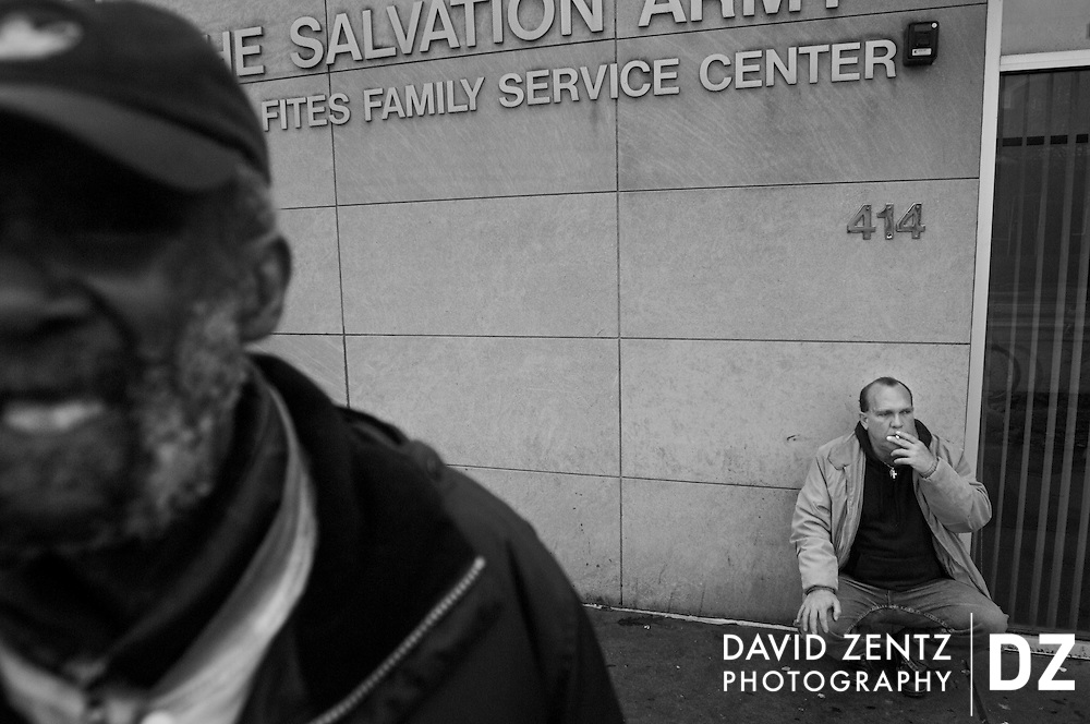 Iaun, 51, smokes a cigarette outside the Salvation Army, where he and other chronically homeless men, such as Gene Richmond, left, spend much of their time.