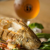 Tilapia Singapore, garnished with FoodChain microgreens, is a specialty dish made by Smithtown Seafood, pictured with a West Sixth Street beer in Lexington, Ky., Friday, December 11, 2015. The Bread Box houses a number of businesses, including West Sixth Brewing and FoodChain, which grows the tilapia. Waste from fish grown in tanks is used to feed greens and the filtered water is looped back into the fish tanks. The fish and greens are sold and used at Smithton Seafood located in the same building, an old Rainbo Bread factory. (Photo by David Stephenson)