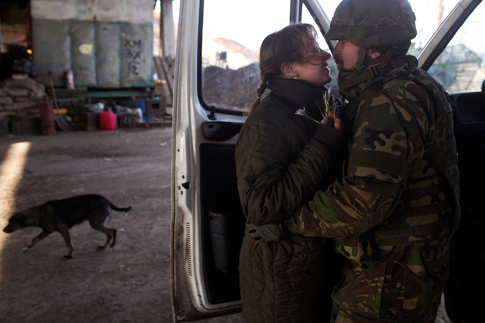 Volodya, a Dnipro-1 battalion volunteer who serves as second-in-command at the bridge, presents his wife with flowers he picked near the front on March 20, 2015 in Pisky, Ukraine.