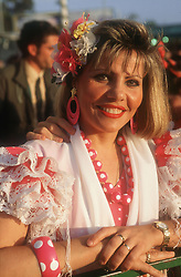 Portrait of woman at the Spring Fair; Seville; wearing Flamenco dress smiling ,