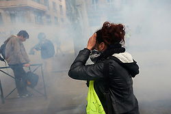 April 27, 2019 - Toulouse, France - A protester tries to protect herself from tear gas. For the Act 24 of the Yellow Vest protest, thousands of  'Gilets jaunes' (ie Yellow vests) protesters demonstrated in Toulouse against French President Macron, his government, its policies. They demand fiscal and social justice, more ecology and the RIC (Citizens Initiated Referendum). They esteem that Fresident Macron has given no answers to their demands. Riot police used volleys of tear gas canisters and water cannon to disperse the crowd. Toulouse. France. April 27th 2019. (Credit Image: © Alain Pitton/NurPhoto via ZUMA Press)