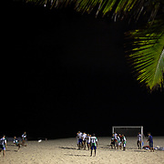 Locals play football at night time under floodlight on the beach at Ipanema beach, Rio de Janeiro, Brazil. 10th July 2010. Photo Tim Clayton..The beaches of Rio de Janeiro, provide the ultimate playground for locals and tourists alike. Beach activity is in abundance as beach volley ball, football and a hybrid of the two, foot volley, are played day and night along the length and breadth of Rio's beaches. .Volleyball nets and football posts stretch along the cities coastline and are a hive of activity particularly at it's most famous beaches Copacabana and Ipanema. .The warm waters of the Atlantic Ocean provide the ideal conditions for a variety of water sports. Walkways along the edge of the beaches along with exercise stations and cycleways encourage sporting activity, even an outdoor gym is available at the Parque Do Arpoador overlooking the ocean. .On Sunday's the main roads along the beaches of Copacabana, Leblon and Ipanema are closed to traffic bringing out thousands of people of all ages to walk, run, jog, ride, skateboard and cycle more than 10 km of beachside roadway. .This sports mad city is about to become a worldwide sporting focus as they play host to the world's biggest sporting events with Brazil hosting the next Fifa World Cup in 2014 and Rio de Janeiro hosting the Olympic Games in 2016...
