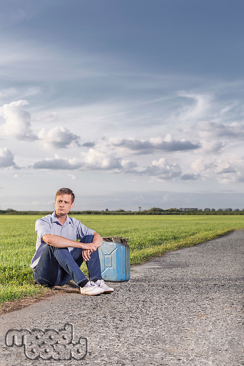Full length of young man with empty petrol can sitting by country road