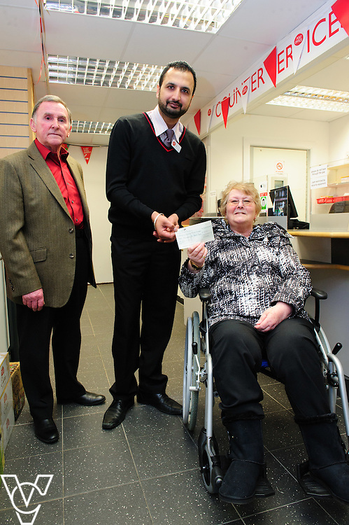 Pictured is Melton Mowbray Post Office postmaster Amarjit Singh, centre, presenting a cheque to Sheila Burdock, right, representing the Melton and Rutland branch of the MS Society.  Also pictured is, Paul Burdock.<br /> <br /> The Mayor of Melton Jeanne Douglas has officially opened the new Post Office in Melton Mowbray.<br /> <br /> Date: March 16, 2016