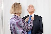 Senior woman adjusting husband's necktie