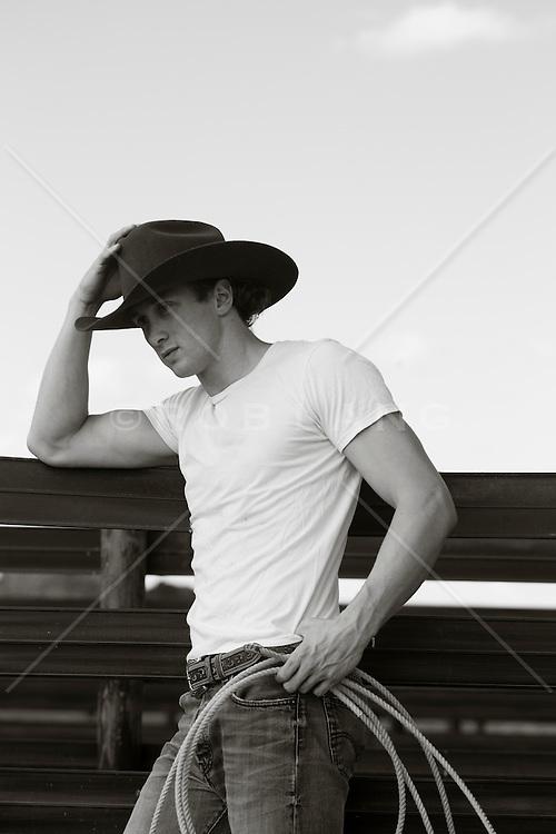 young good looking cowboy wearing a white tee shirt and cowboy hat at a ranch