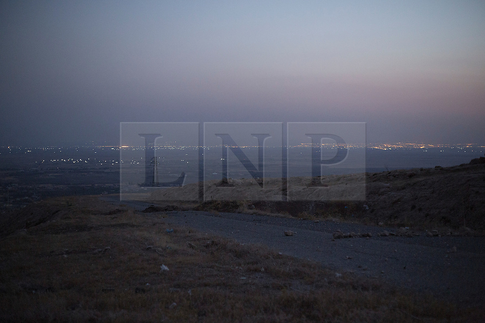 © Licensed to London News Pictures. 01/09/2015. Bashiqa, Iraq. Lights coming from Islamic State held Mosul, Iraq's second largest city, are seen from Kurdish peshmerga defensive positions on Bashiqa Mountain.<br /> <br /> Bashiqa Mountain, towering over the town of the same name, is now a heavily fortified front line. Kurdish peshmerga, having withdrawn to the mountain after the August 2014 ISIS offensive, now watch over Islamic State held territory from their sandbagged high-ground positions. Regular exchanges of fire take place between the Kurds and the Islamic militants with the occupied Iraqi city of Mosul forming the backdrop.<br /> <br /> The town of Bashiqa, a formerly mixed town that had a population of Yazidi, Kurd, Arab and Shabak, now lies empty apart from insurgents. Along with several other urban sprawls the town forms one of the gateways to Iraq's second largest city that will need to be dealt with should the Kurds be called to advance on Mosul. Photo credit: Matt Cetti-Roberts/LNP