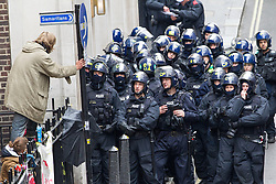 © Licensed to London News Pictures . 11/06/2013 . London , UK . A protester leans over from the edge of the property , watched by dozens of riot police . Police surround a former police station on 40 Beak Street , Soho this morning (11th June) . The site has been occupied by organisers of today's Stop G8 anti capitalist protests . Demonstrations in London today (Tuesday 11th June 2013) ahead of Britain hosting the 39th G8 summit on 17th/18th June at the Lough Erne Resort , County Fermanagh , Northern Ireland , next week . Photo credit : Joel Goodman/LNP