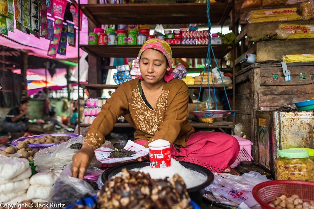 14 JUNE 2013 -  PANTANAW, AYEYARWADY, MYANMAR: A Muslim merchant sells sugar in the market in Pantanaw, in the Ayeyarwady Region of south-west Myanmar. It is the hometown of former United Nations Secretary-General U Thant and of the renowned artist U Ba Nyan.   PHOTO BY JACK KURTZ