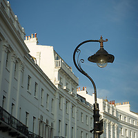 Large Georgian homes in Sussex Gardens, Brighton, East Sussex, England with old street lamp in summer under blue sky