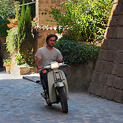 Man riding motorscooter Civita di Bagnoregio, Italy<br />