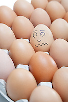 Funny face drawn on an egg surrounded by plain brown eggs in carton